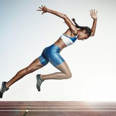 The Young african woman running on runing track on white background. Studio shot